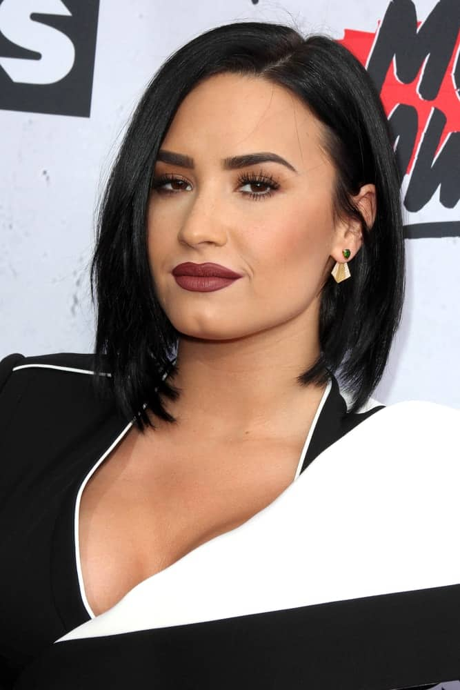 Demi Lovato wore a fashionable black and white outfit that she paired with matte red lips and short, straight raven hairstyle at the iHeart Radio Music Awards 2016 Arrivals at the The Forum on April 3, 2016 in Inglewood, CA.