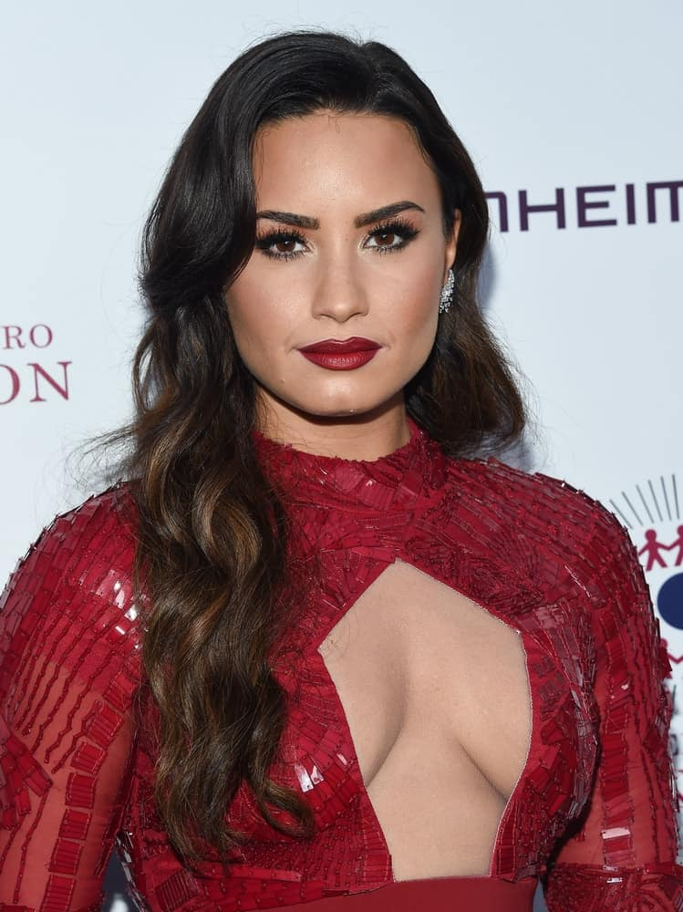 Demi Lovato flaunted her lovely red lips with her red dress and beautiful side-swept wavy hairstyle with highlights and side-swept bangs at the 2017 Brent Shapiro Foundation Summer Spectacular on September 9, 2017 in Beverly Hills, CA.