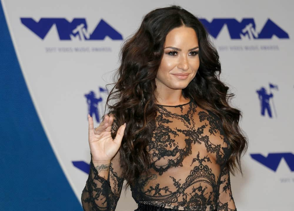 Demi Lovato wowed everyone with her stunning sheer black dress that she paired with her long and wavy hairstyle that has a tousled loose finish at the 2017 MTV Video Music Awards held at the Forum in Inglewood, USA on August 27, 2017.