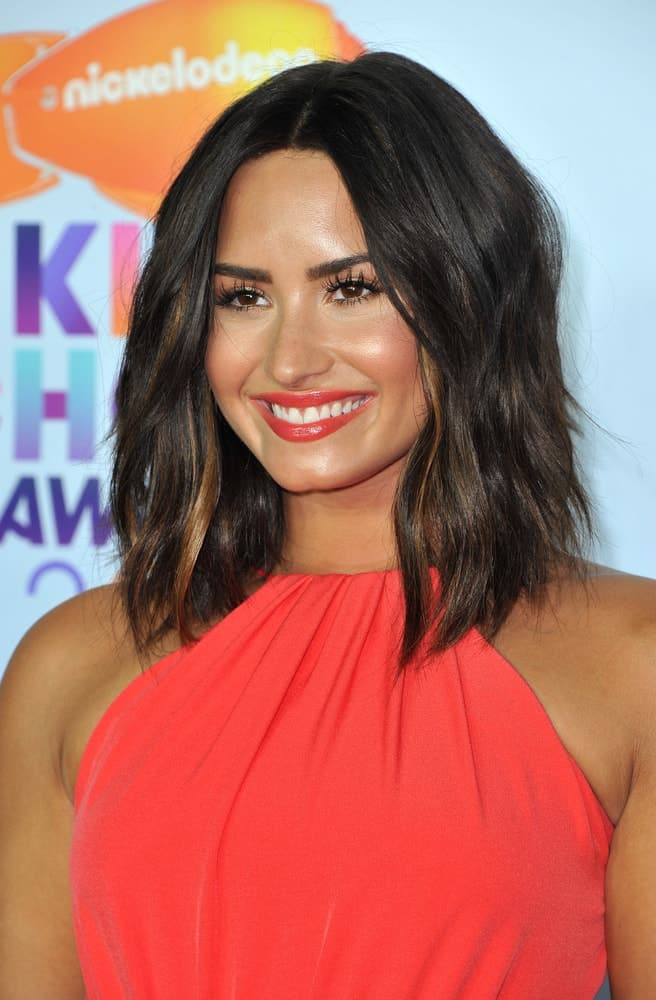 Demi Lovato paired her lovely dress with bold red lips and shoulder-length wavy tousled hairstyle with highlights at the Nickelodeon's 2017 Kids' Choice Awards held at the USC Galen Center in Los Angeles, USA on March 11, 2017.