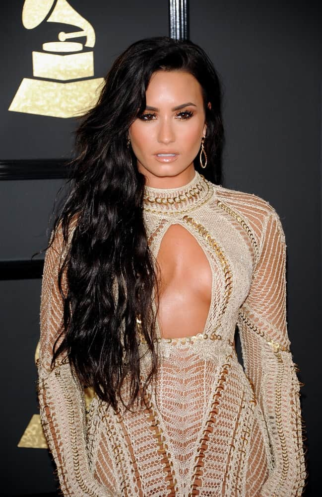 Demi Lovato was quite charming in her white sheer dress and side-swept layered long raven hairstyle with waves and long side-swept bangs at the 59th GRAMMY Awards held at the Staples Center in Los Angeles, USA on February 12, 2017.
