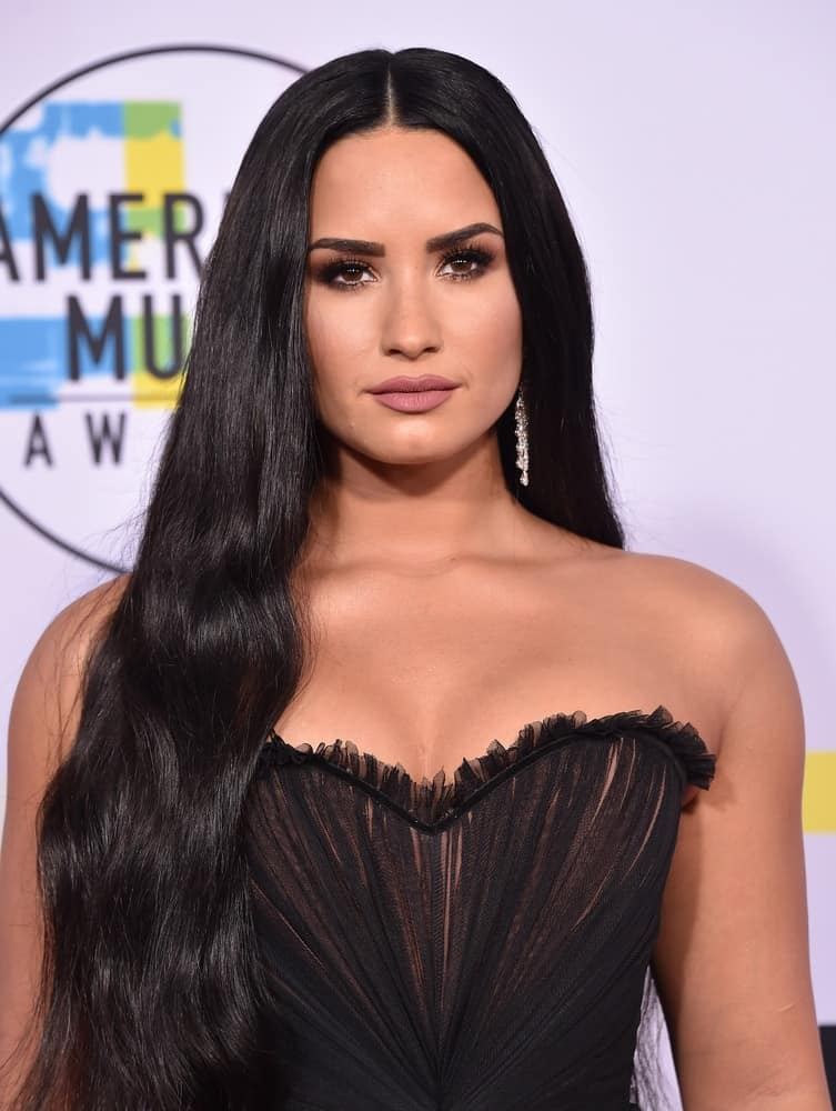 Demi Lovato attended the 2017 American Music Awards on November 19, 2017 in Los Angeles, CA. She wore a sexy strapless black dress to match with her raven long and straight hairstyle with subtle waves at the tips.