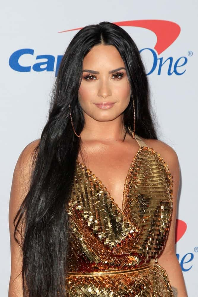 Demi Lovato wore a shiny golden dress to pair with her long layered raven hairstyle loose on her shoulders at the Jingle Ball 2017 at the Forum on December 2, 2017 in Inglewood, CA.