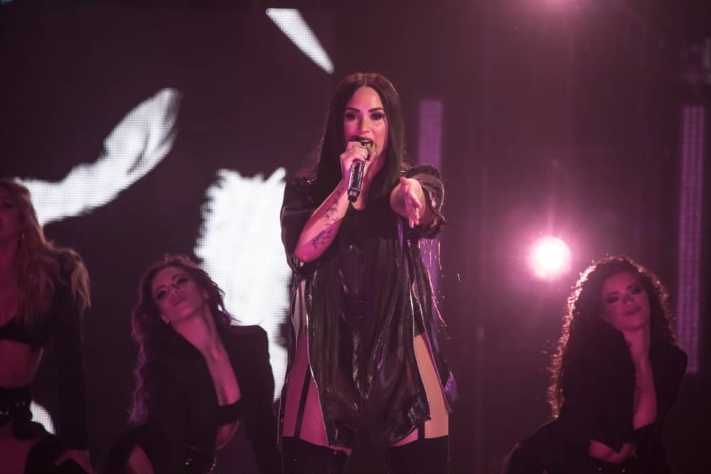On March 13, 2018, Demi Lovato performed at Little Caesars Arena on her Tell Me You Love Me world tour in Detroit, Miami. She wore a sexy black outfit that she paired with her long and straight raven hairstyle that has a slight tousled finish.