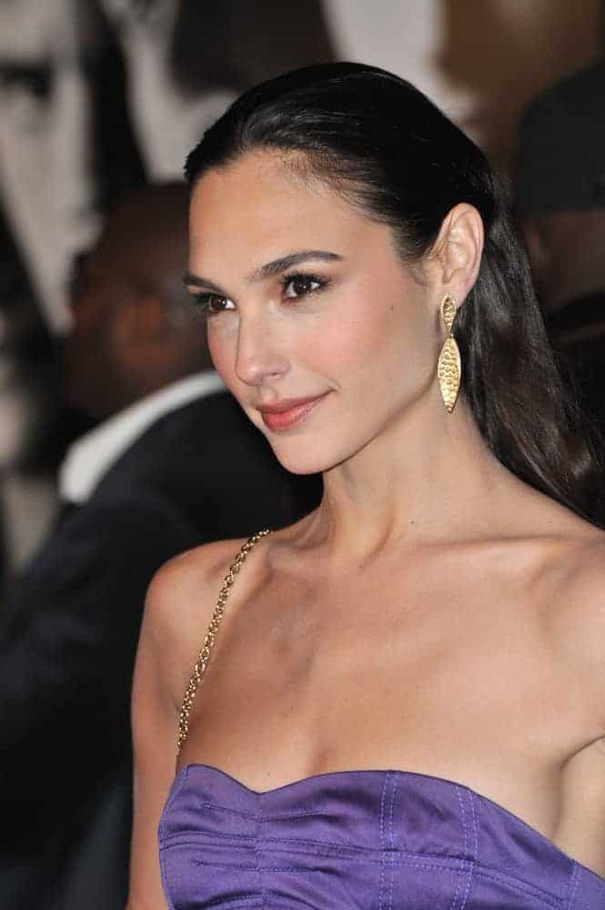 """Gal Gadot was at the world premiere of her new movie """"Fast & Furious"""" at the Gibson Amphitheatre, Universal Studios, Hollywood on March 12, 2009. She came in a stunning purple strapless dress paired with a slicked-back raven hairstyle."""