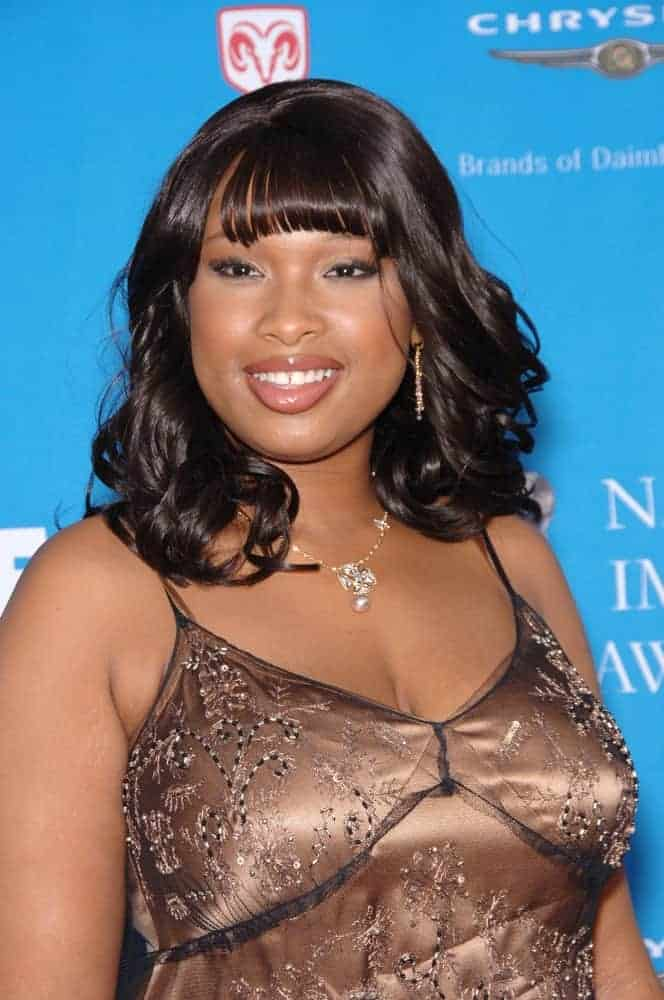 Jennifer Hudson was at the 37th Annual NAACP Image Awards at the Shrine Auditorium in Los Angeles on February 25, 2006. She wore a golden dress that she paired with a tousled curly shoulder-length hairstyle that has blunt bangs.