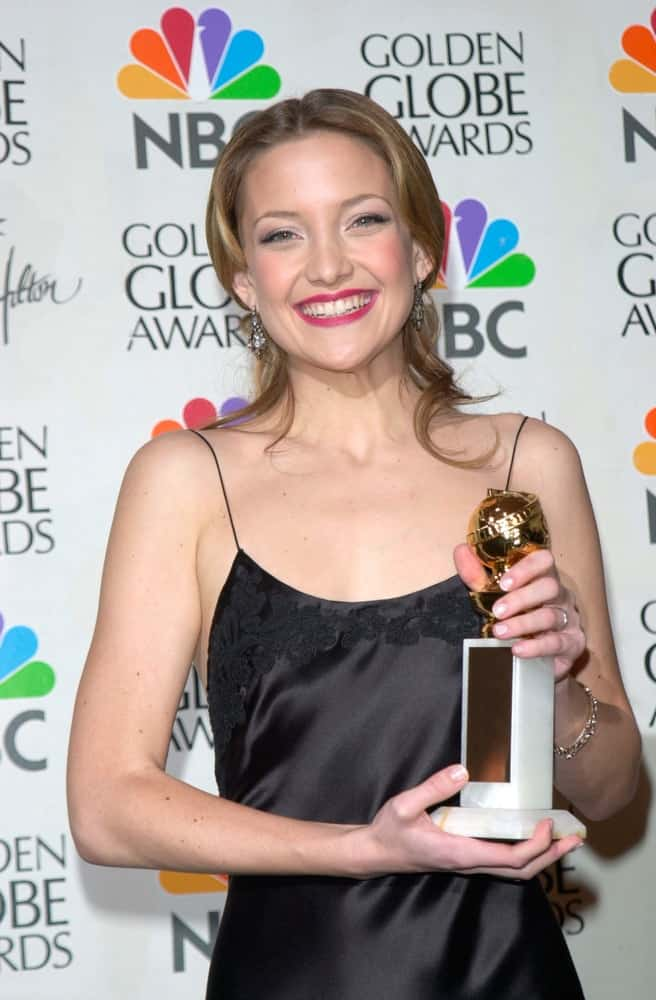 Actress Kate Hudson held her hard-earned trophy at the 2001 Golden Globe Awards at the Beverly Hilton Hotel on January 21, 2001. She came wearing a simple black silk dress that she paired with a half-up hairstyle with curls at the tips and a brownich tone.