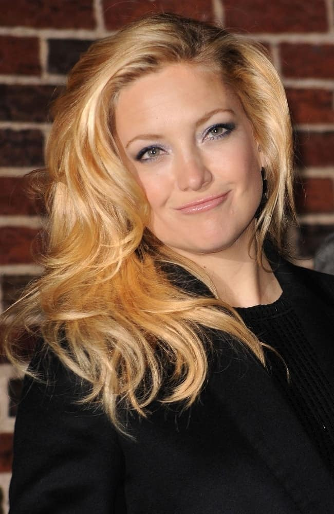 Kate Hudson was at a talk show appearance for The Late Show with David Letterman at the Ed Sullivan Theater in New York, NY on December 14, 2009. She wore a black smart casual jacket with her side-swept and tousled wavy blond layers.