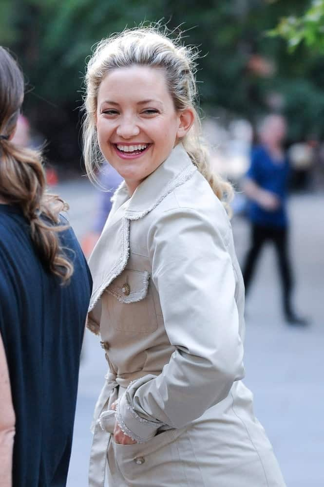 Kate Hudson was seen at the 'Something Borrowed' movie set in New York, NY on June 2, 2010. She was wearing a trench coat with her bright smiles and messy low ponytail hairstyle with loose blond tendrils.