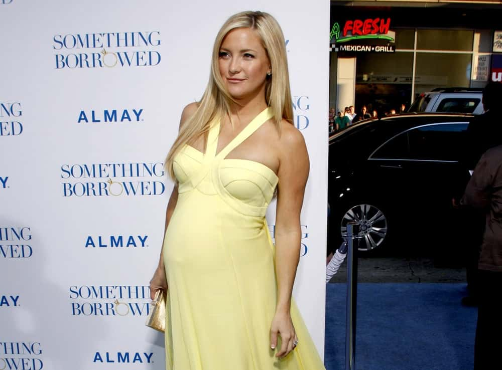 Kate Hudson had that pregnant glow that she complemented with a yellow dress and a loose layered straight blond hairstyle with side-swept bangs at the Los Angeles Premiere of