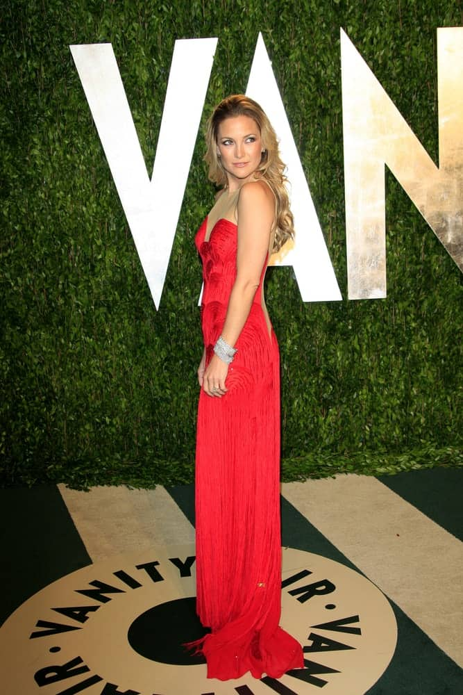 Kate Hudson's elegant long red dress went quite well with her long and layered wavy blond hairstyle loose on her back at the Vanity Fair Oscar Party at Sunset Tower on February 26, 2012 in West Hollywood, California.
