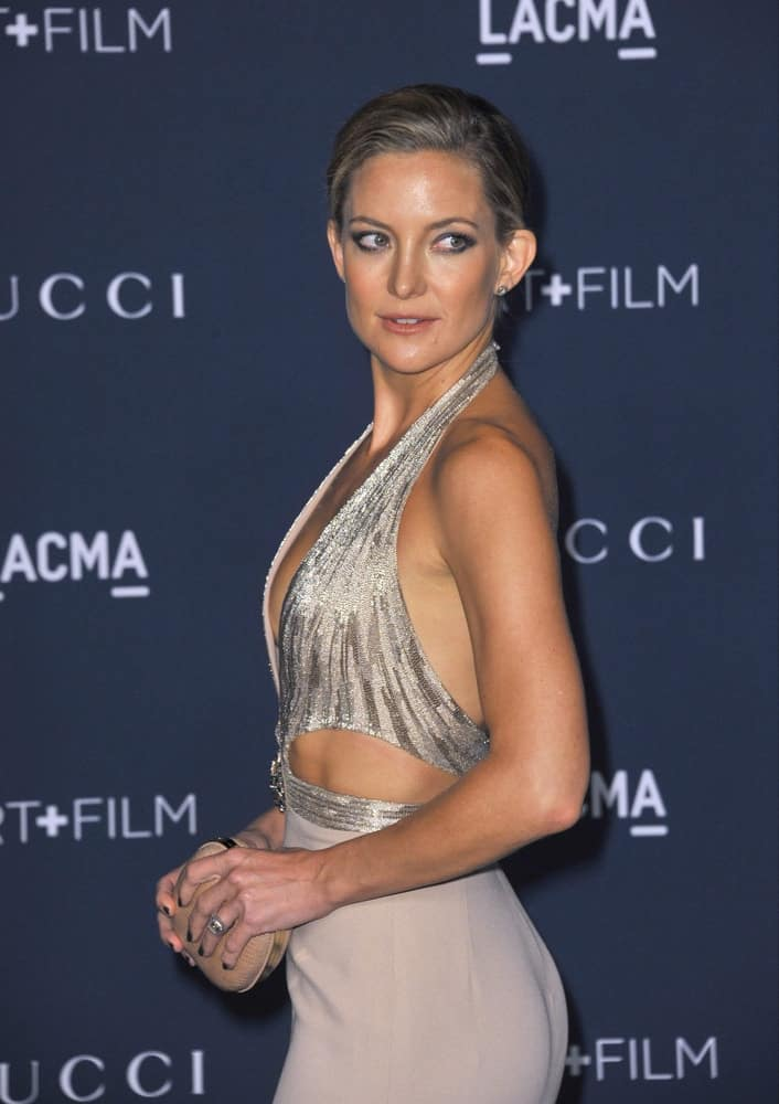 On November 2, 2013, Kate Hudson wore a silver detailed dress that she paired with her neat side-parted bun hairstyle that has metallic highlights at the 2013 LACMA Art+Film Gala at the Los Angeles County Museum of Art.