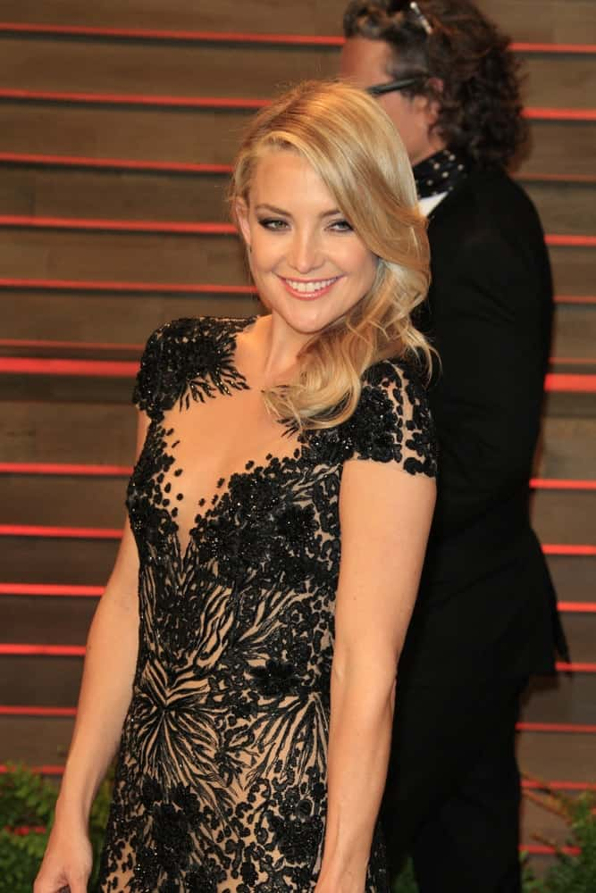 Kate Hudson stole the show with her lovely black dress with floral patterns that she paired with her side-swept wavy blond hairstylethat has long side-swept bangs at the 2014 Vanity Fair Oscar Party at the Sunset Boulevard on March 2, 2014 in West Hollywood, CA.