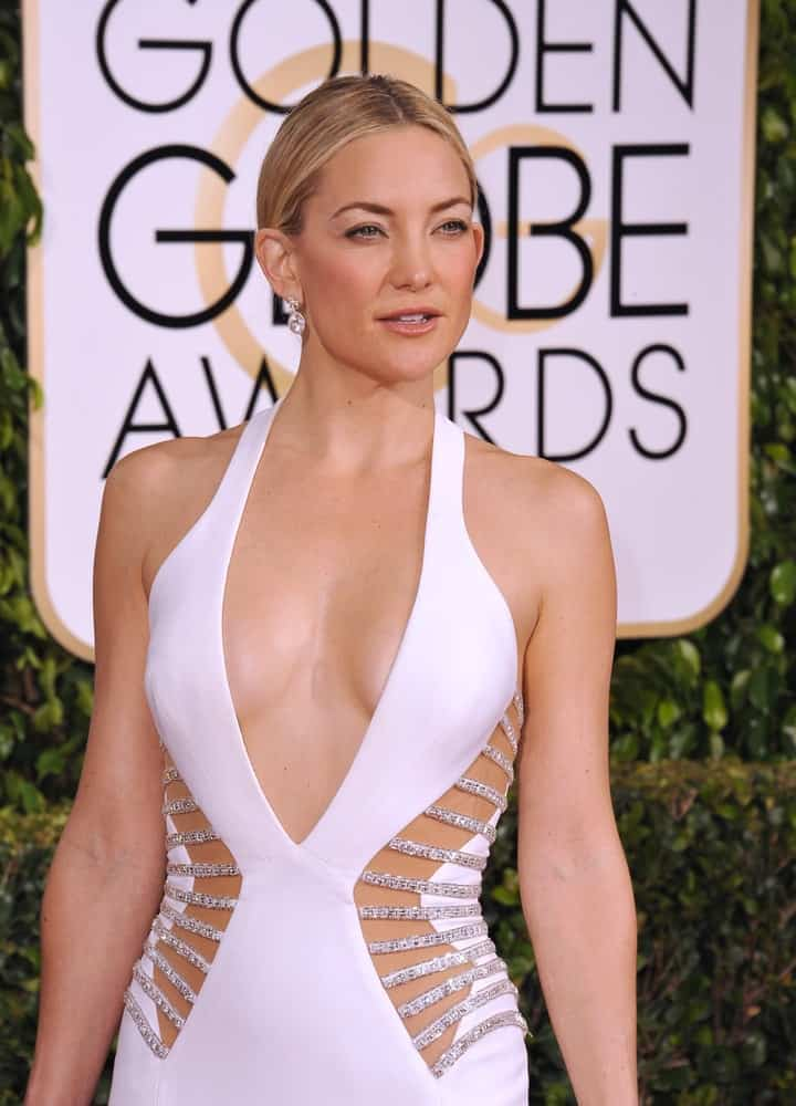 On January 11, 2015, Kate Hudson wore an elegant and sexy white dress that flaunted her physique paired with a simple bun hairstyle at the 72nd Annual Golden Globe Awards at the Beverly Hilton Hotel, Beverly Hills.