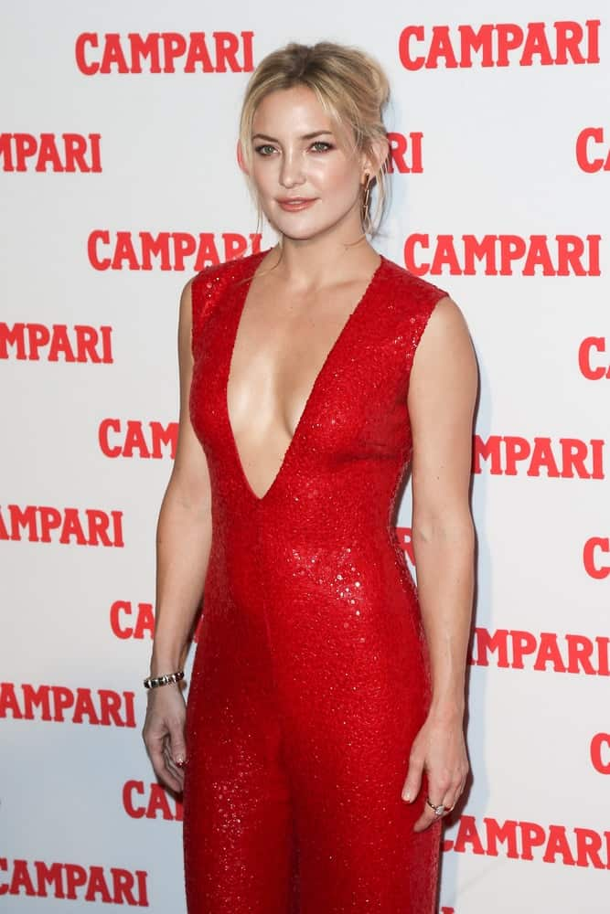 Actress Kate Hudson wowed the crowd with her stunning red jumpsuit outfit that went quite well with her messy bun hairstyle with loose blond tendrils at the 2016 Campari Calendar Launch Event at The Standard Hotel on November 18, 2015 in New York City.