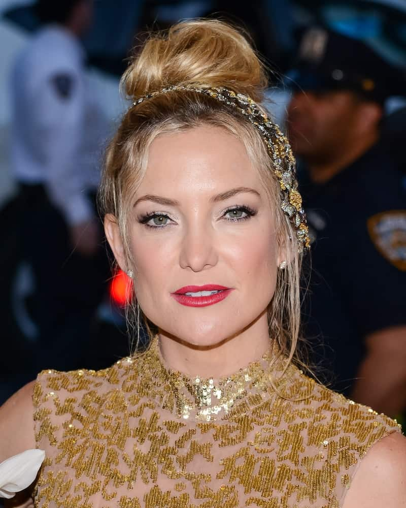 On May 04, 2015, Kate Hudson attended the 'China: Through The Looking Glass' Costume Institute Gala held at the Metropolitan Museum of Art in New York City, New York. She wore a gold sequined sheer dress with her messy top knot bun hairstyle with loose tendrils.