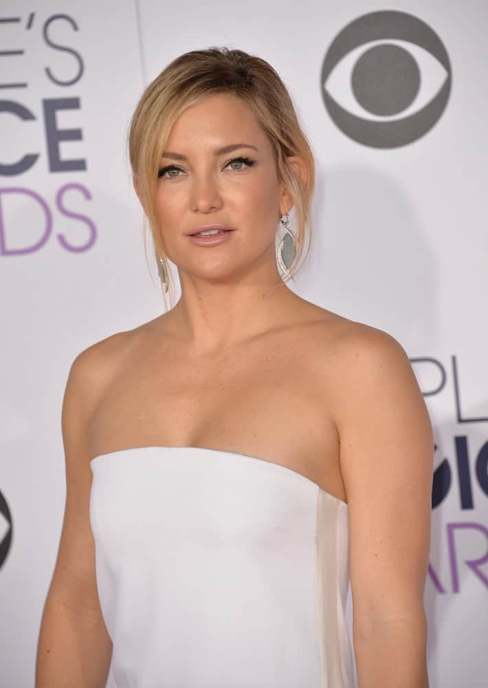 On January 6, 2016, Kate Hudson went with a simple yet charming look to her white strapless dress and messy bun hairstyle that has loose side-swept bangs and tendrils at the People's Choice Awards 2016.
