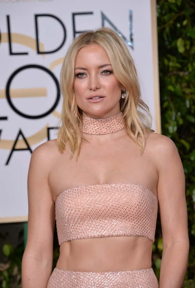 On January 10, 2016, Kate Hudson was at the 73rd Annual Golden Globe Awards at the Beverly Hilton Hotel. She flaunted her tone physique with a two-piece pink patterned outfit and a loose and wavy sandy blond hairstyle on her shoulders.
