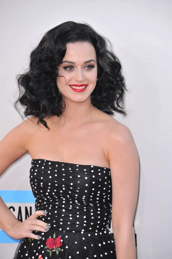 Katy Perry matched her black tube dress with a tousled curly hairstyle during the 2013 American Music Awards at the Nokia Theatre, LA Live on November 24, 2013.