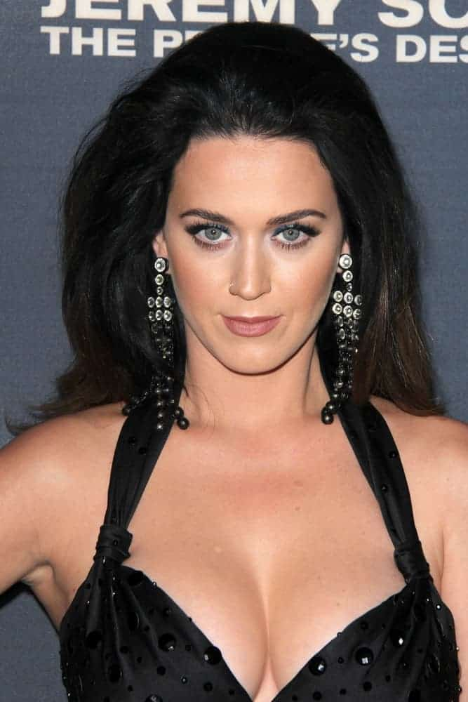 Katy Perry in an eccentric and eye-catching black dress with a high slit and bow detail. At the top, framing her beautiful face is a slicked back textured hair, a dramatic hairstyle she wears at the