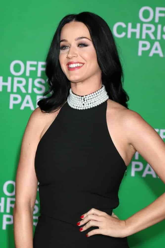 Katy Perry rocks in black with her elegant black sleeveless gown and her medium-length raven hair was sleekly styled into loose big curls with center part during the
