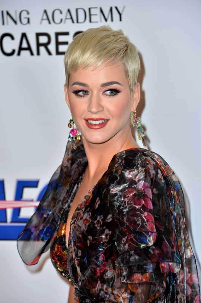 Katy Perry went for a pixie cut emphasizing her colorful chandelier earrings at the 2019 MusiCares Person of the Year Gala honoring Dolly Parton on February 8, 2019.