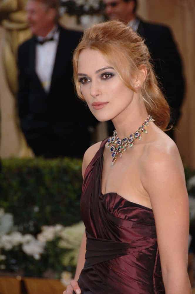 Keira Knightley at the 78th Annual Academy Awards at the Kodak Theatre in Hollywood on March 5, 2006, in Los Angeles, CA. She wore a stunning shiny maroon dress that went well with her sandy blond ponytail hairstyle incorporated with long side bangs.