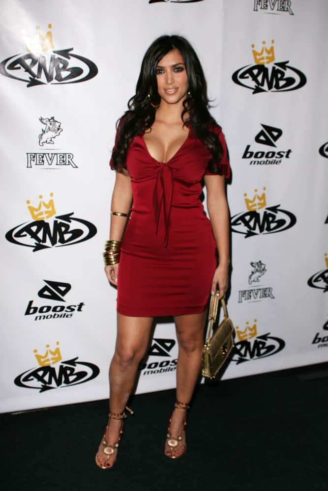 Kim Kardashian opted for a side-parted curly hairstyle to go with her red dress at thebirthday party for Nick Cannon and the opening of his flagship store for PNB Nation on October 10, 2006.