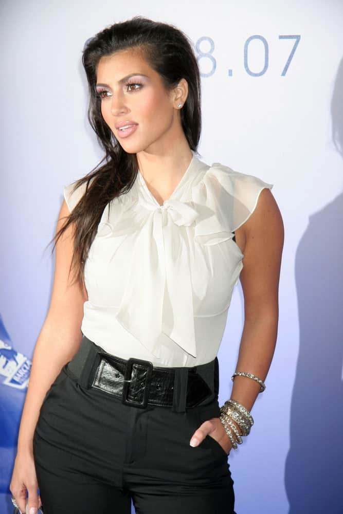Kim Kardashian with her loose slicked back hair at the Chelsea Football Club Hollywood Party held on July 18, 2007. She finished the look with a white sheer top and black pants with a statement belt.