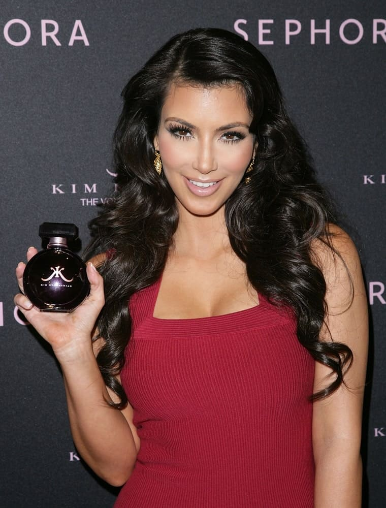 Kim Kardashian at an in-store appearance for Kim Kardashian Fragrance Launch on February 4, 2010, flaunting her voluminous side-parted waves paired with a red dress.