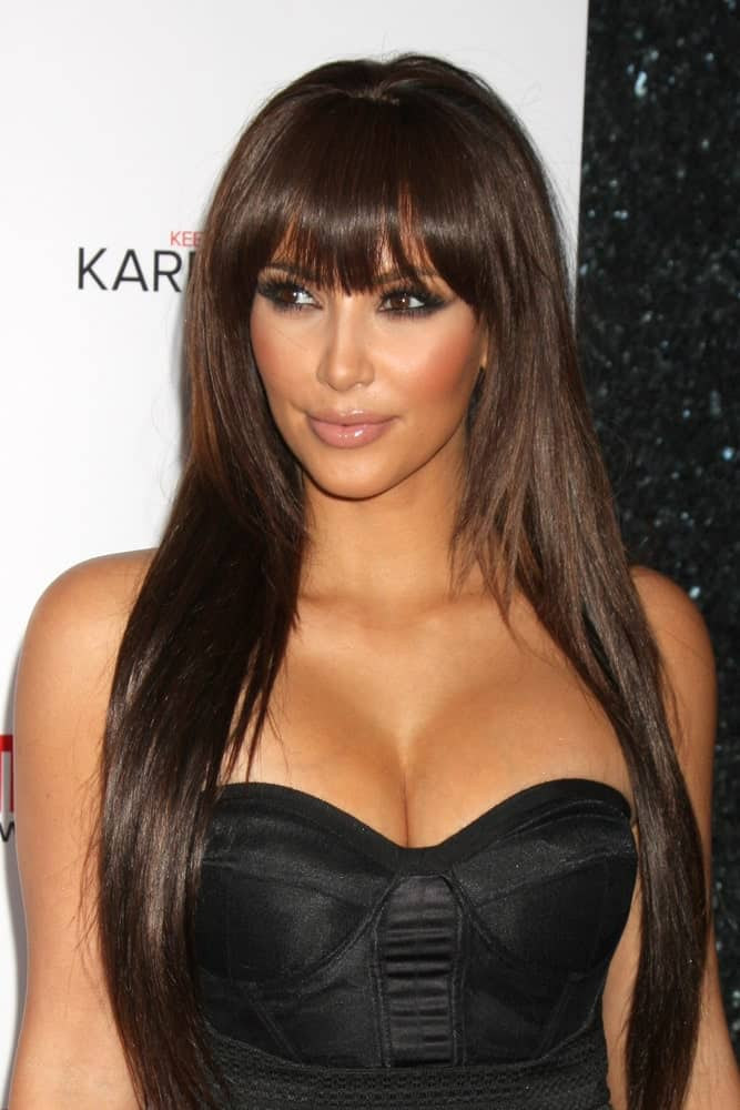 Kim Kardashian opted for straight layered hair with eye skimming bangs at the