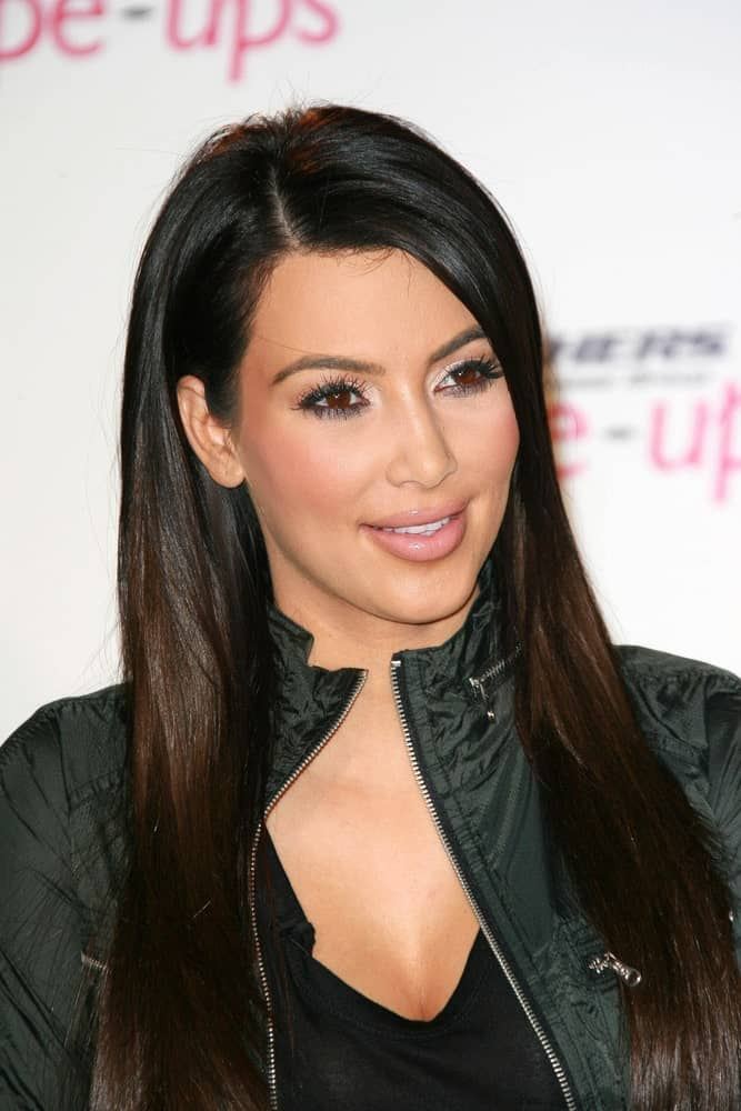 Kim Kardashian at a press conference to announce a Global Partnership With Kim Kardashian And Kris Jenner on November 22, 2010, sporting her straight long locks with a side part.