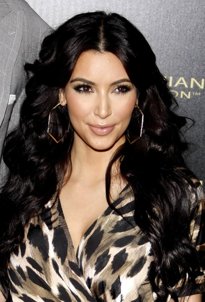 Kim Kardashian paired her printed jumpsuit with voluminous center-parted curls at the Kardashian Kollection Launch Party held at the Colony in Hollywood, USA on August 17, 2011.