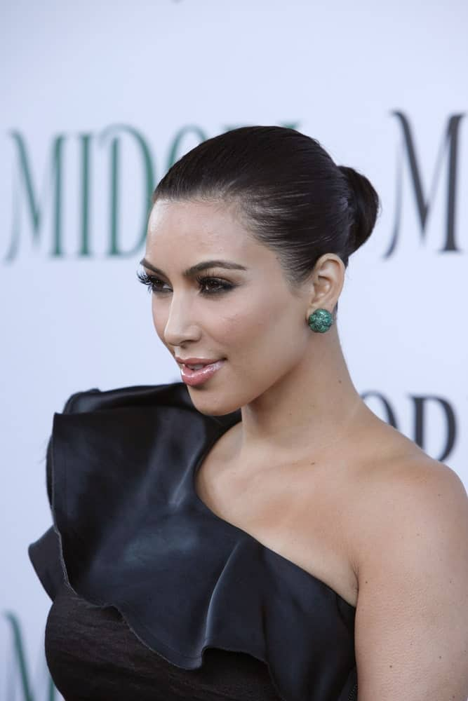 Kim Kardashian matched her black one-shoulder dress with a neat bun at the Midori Melon Liqueur Trunk Show at Trousdale on May 10, 2011.
