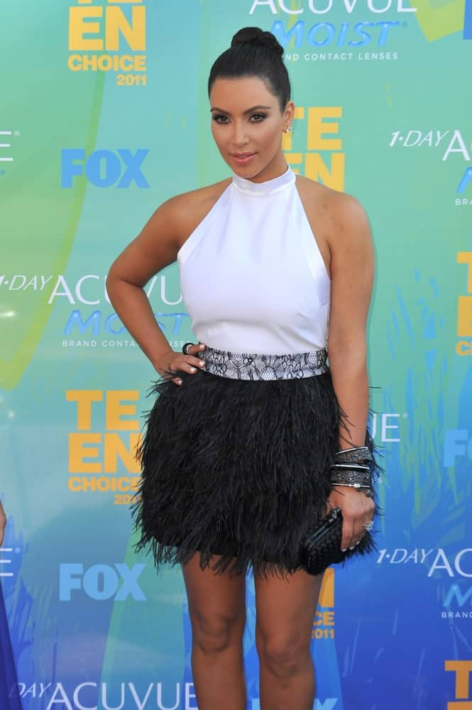 Kim Kardashian complements her slicked high bun with a contrasting white halter top and black fringe skirt during the 2011 Teen Choice Awards at the Gibson Amphitheatre, Universal Studios, Hollywood held on August 7, 2011.