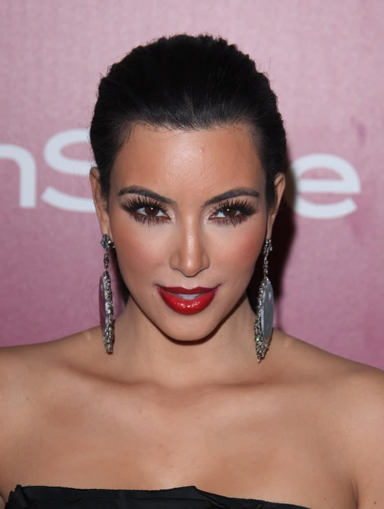 Kim Kardashian rocked a neat updo emphasizing her dangling earrings at the 12th Annual WB-In Style Golden Globe After Party on January 16, 2011.