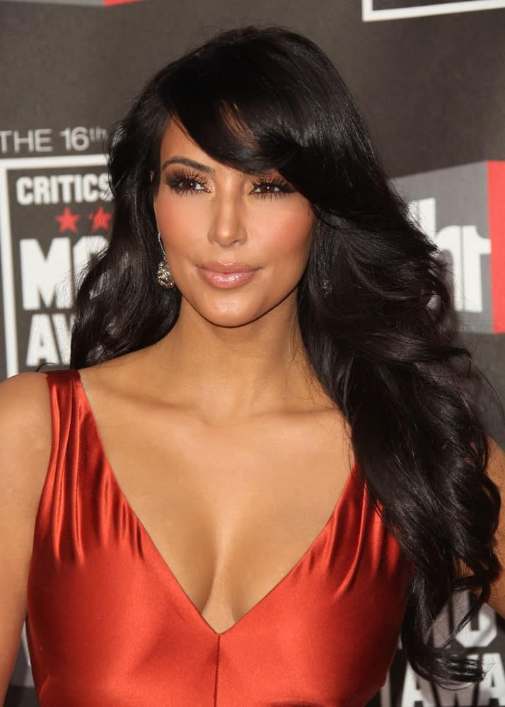 Kim Kardashian styled her long raven hair with twisted curls and side-swept bangs during the 16th Annual