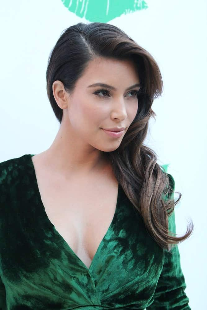 Kim Kardashian gathered her wavy locks on one side and styled it with a deep side part during the Midori Makeover Parlour at Fred Segal on September 25, 2012.