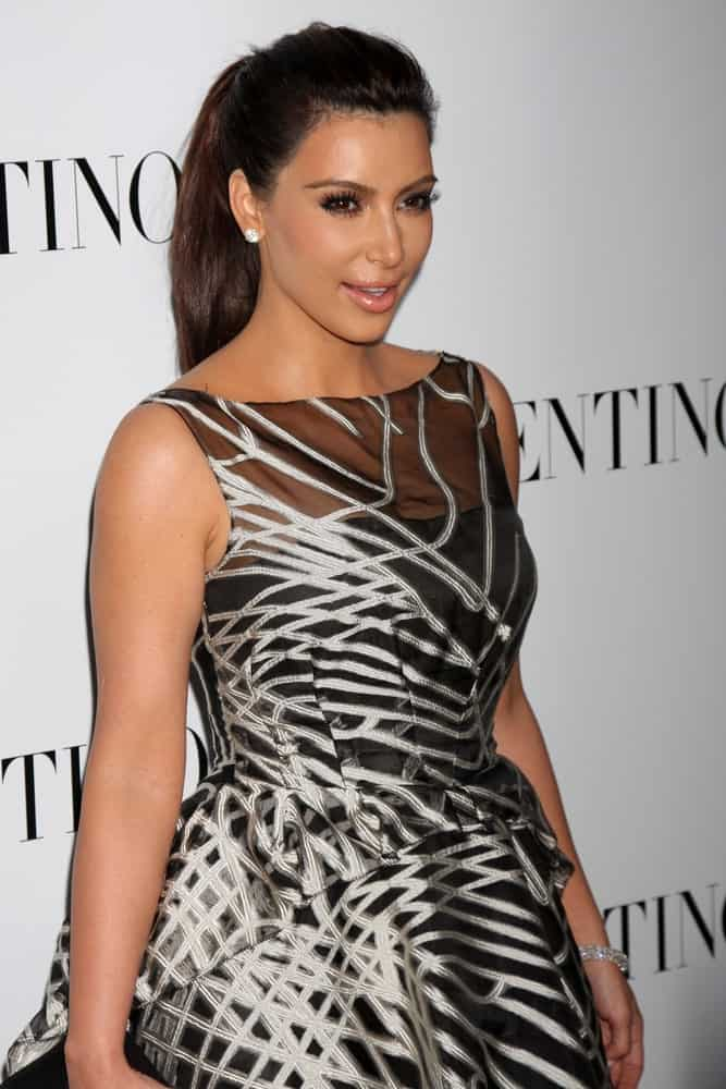 Kim Kardashian complements her printed dress with a brunette high ponytail during the Valentino Beverly Hills Opening at the Valentino Store on March 27, 2012.