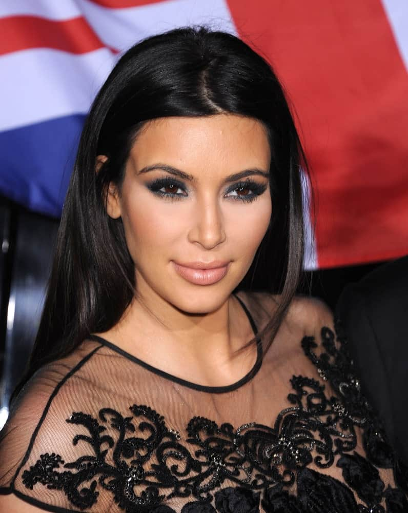 Kim Kardashian pulled off her usual center-parted loose hairstyle that's paired with a sophisticated black lace gown at the Topshop Topman Store Opening Party on February 13, 2013.
