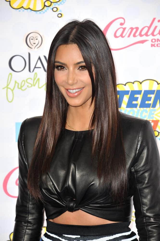 Kim Kardashian opted for a long layered hairstyle with a middle parting at the 2014 Teen Choice Awards at the Shrine Auditorium held on August 10, 2014.
