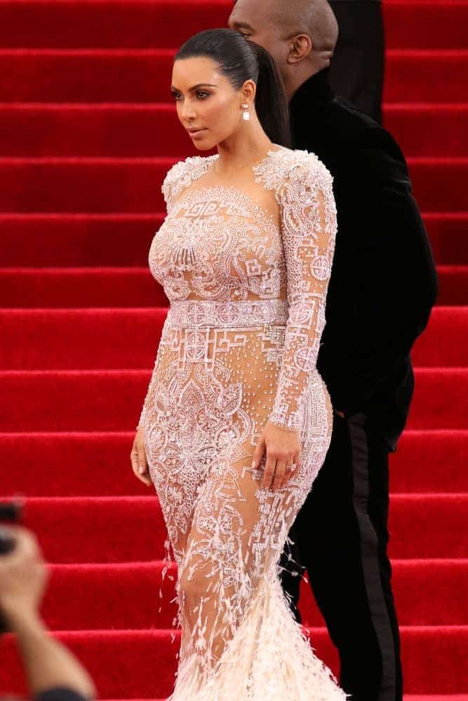 Kim Kardashian dares to bare in a white sheer embellished gown and pulled her dark locks back into a firmed ponytail, proving once again just how fierce and confident she truly is while attending the Costume Institute benefit gala.