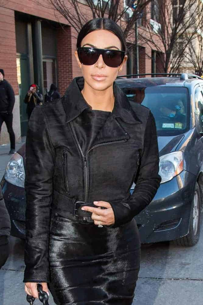 Kim Kardashian was seen wearing an Adidas track jacket under a silk slip dress with her sleek pulled back middle part ponytail while sighting in SoHo.