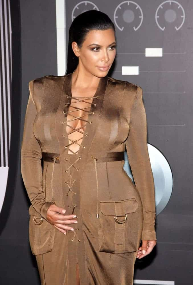 Kim Kardashian showed off her baby bump in a camo colored full-length dress and she was absolutely glowing with this sexy long slicked back hairstyle during the 2015 MTV Video Music awards.