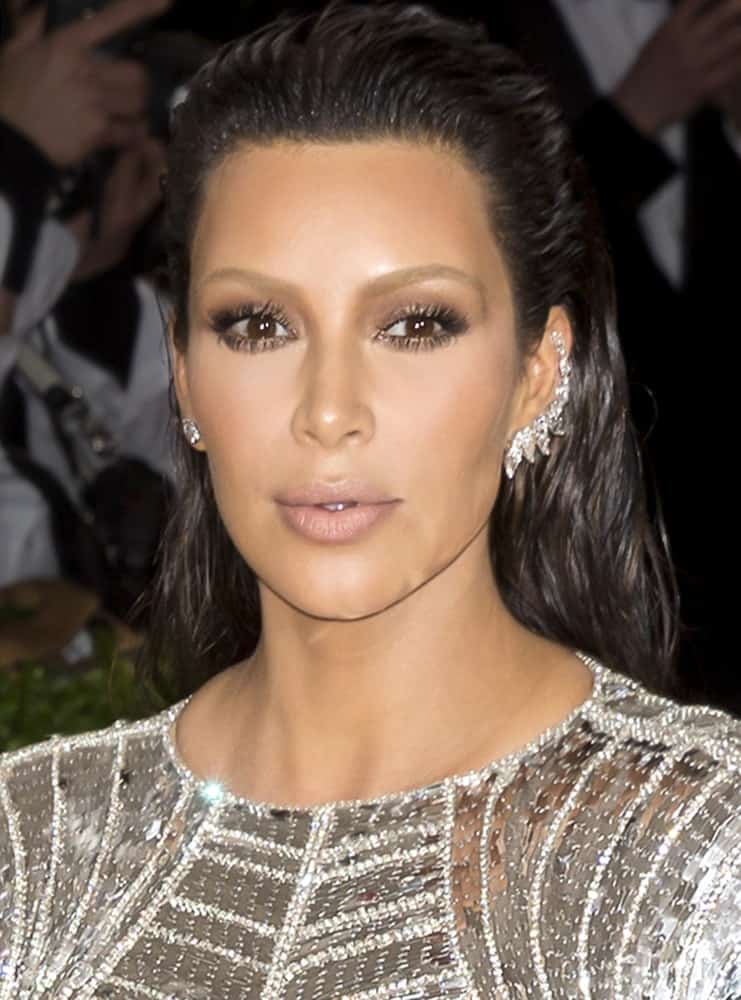 Kim Kardashian dazzled in a silver metallic long sleeve gown and gave a fresh vibe with her slicked back wet hair look as she attends the 2016 MET gala.