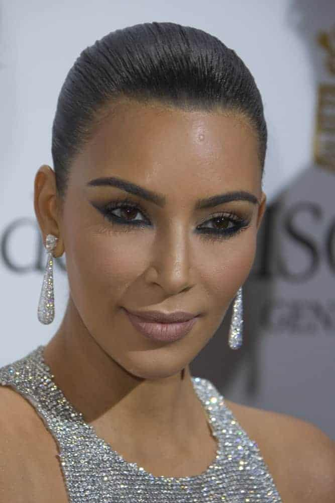Kim Kardashian displays her signature curves in a sparkling silver chainmail gown and she looks flawless with her raven locks pinned back in a tight bun as she attends the annual 69th Cannes Film Festival.