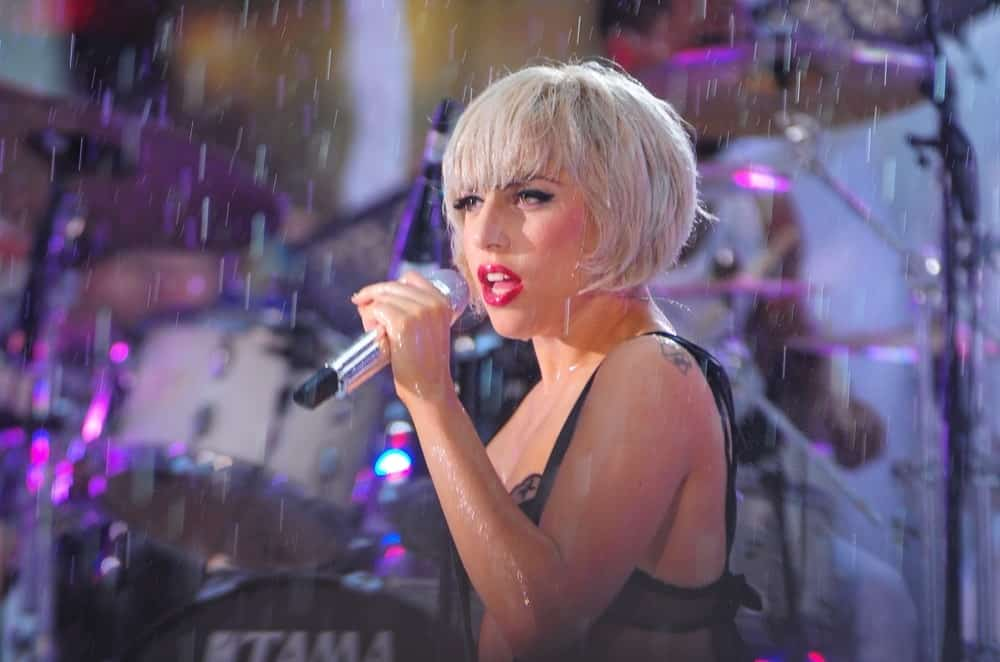 Lady Gaga was on stage for NBC Today Show Concert with Lady Gaga in Rockefeller Plaza, New York on July 9, 2010. Despite the rain, she looked lovely with her bold red lips and matching short platinum blond hairstyle with blunt bangs.