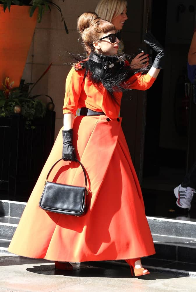 Lady Gaga was seen leaving her hotel on November 9, 2011 in London. She paid homage to Holloween with her pumpkin-colored dress, cool sunglasses and an Audrey Hepburn style hairstyle that has a top knot bun with short blunt bangs.