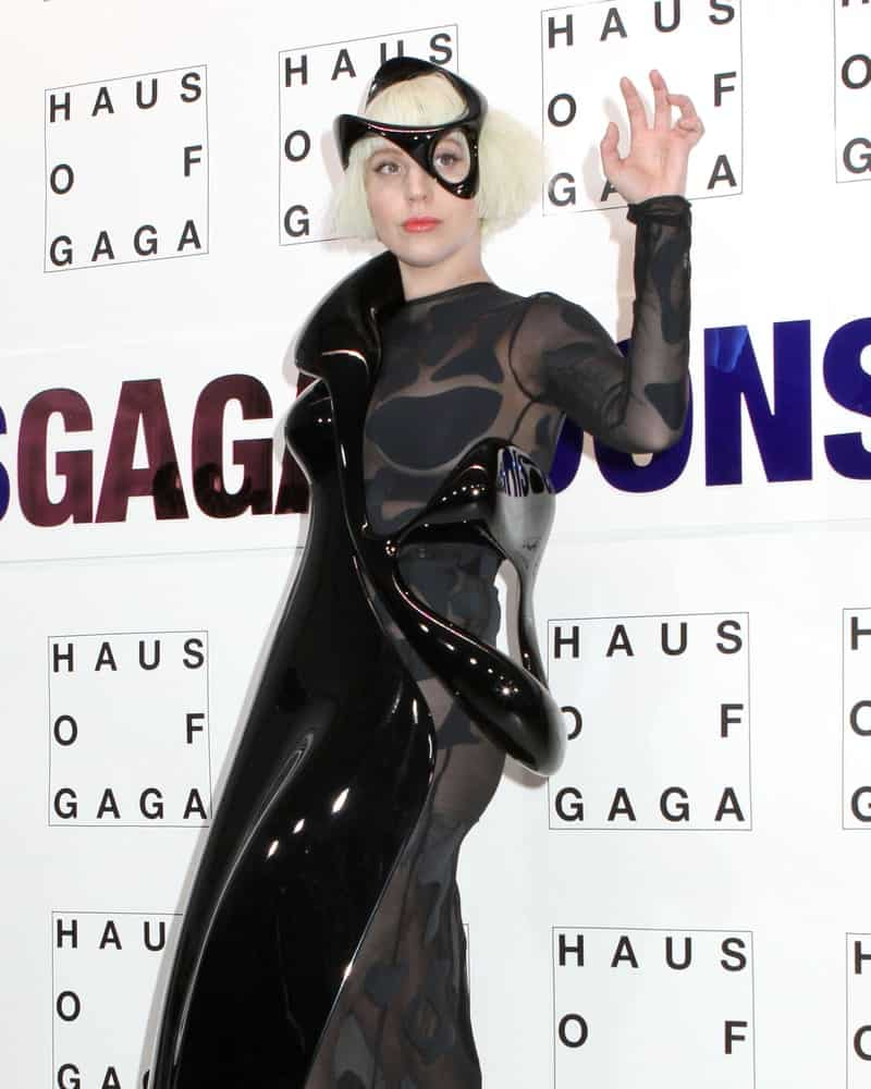 Lady Gaga attends the record release party event for her new album 'ARTPOP' at the Brooklyn Navy Yard on November 10, 2013 in New York. She appeared in a black sheer dress with a shiny black artistic sculpture attached on it that pairs with the black headdress contrasted by her short straight light blond hair with blunt bangs.