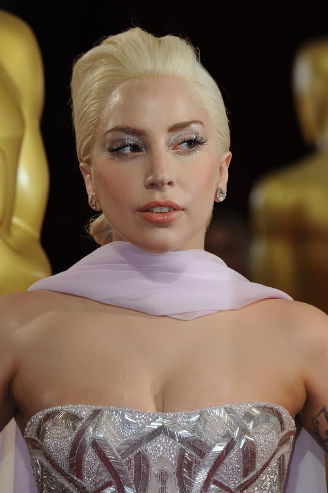 On March 2, 2014, Lady Gaga was at the 86th Annual Academy Awards at the Hollywood & Highland Theatre, Hollywood. She wowed everyone in her stunning silver shiny strapless dress that she topped with a classy low bun hairstyle with a slight pompadour finish.